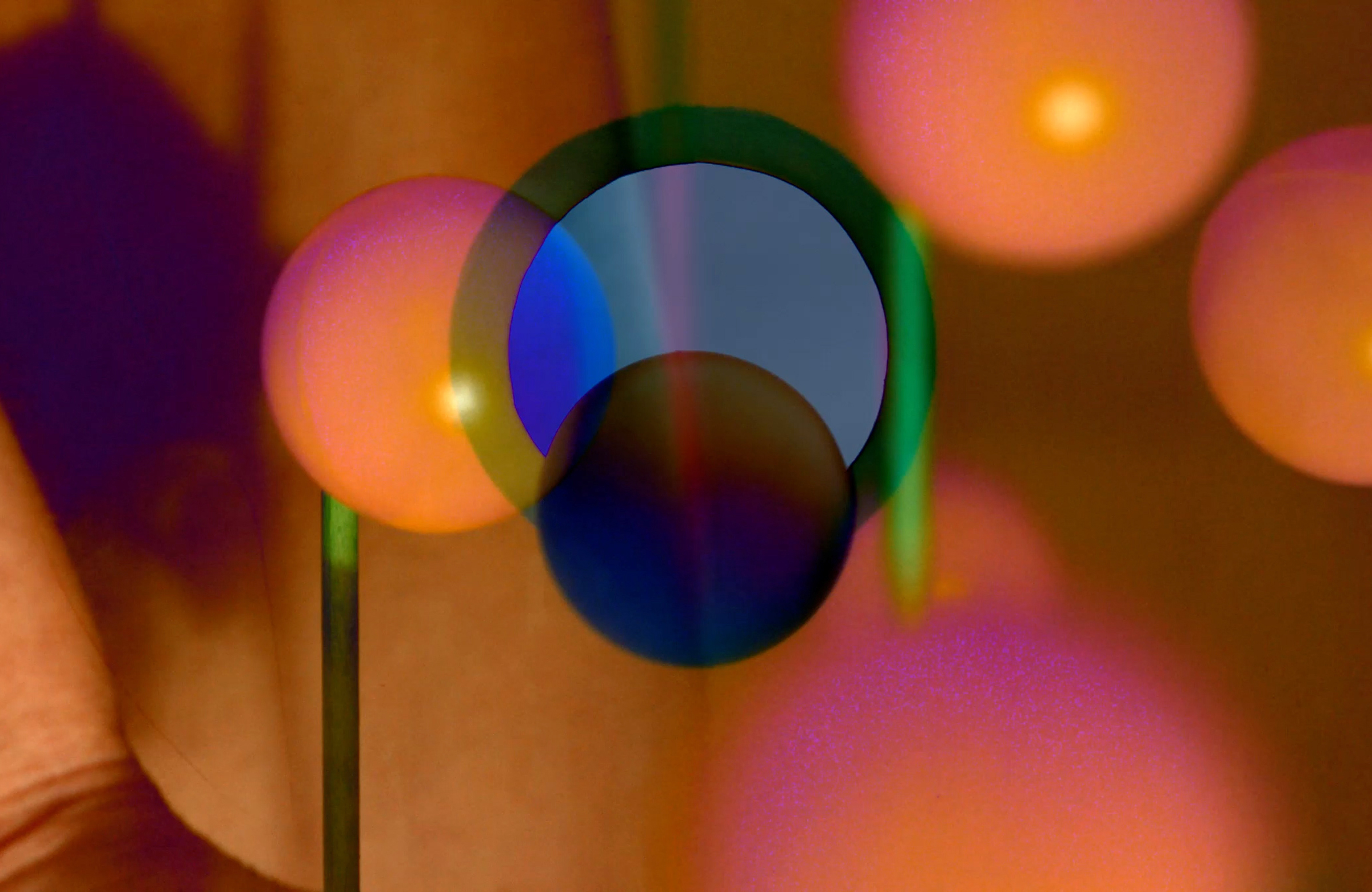 an abstract image of orange and pink blurred spheres with 2D blue toned circles in the foreground of the image