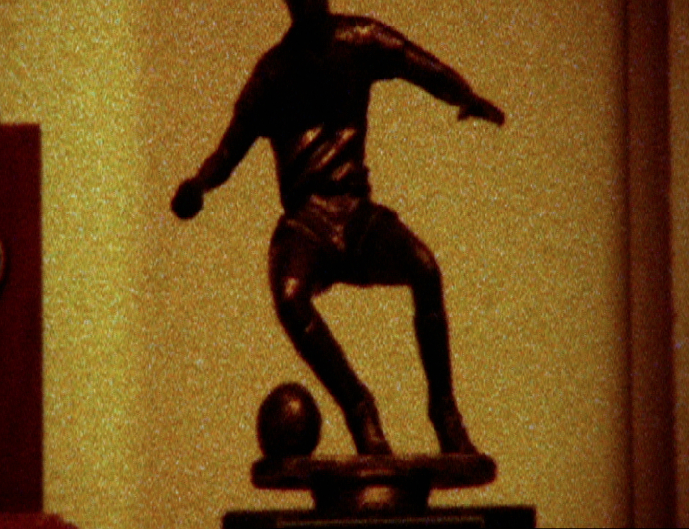 The image is a grainy film still from the Genome Chronicles by John Akomfrah showing a cropped image of a trophy on a yellow background. The trophy has a representation of a football player kicking a ball on top of it, it is cropped so that the head of the football player is not visible.