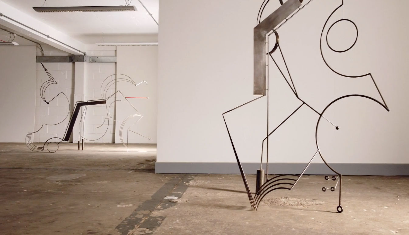 two metal sculptures consisting of various intricate shapes
