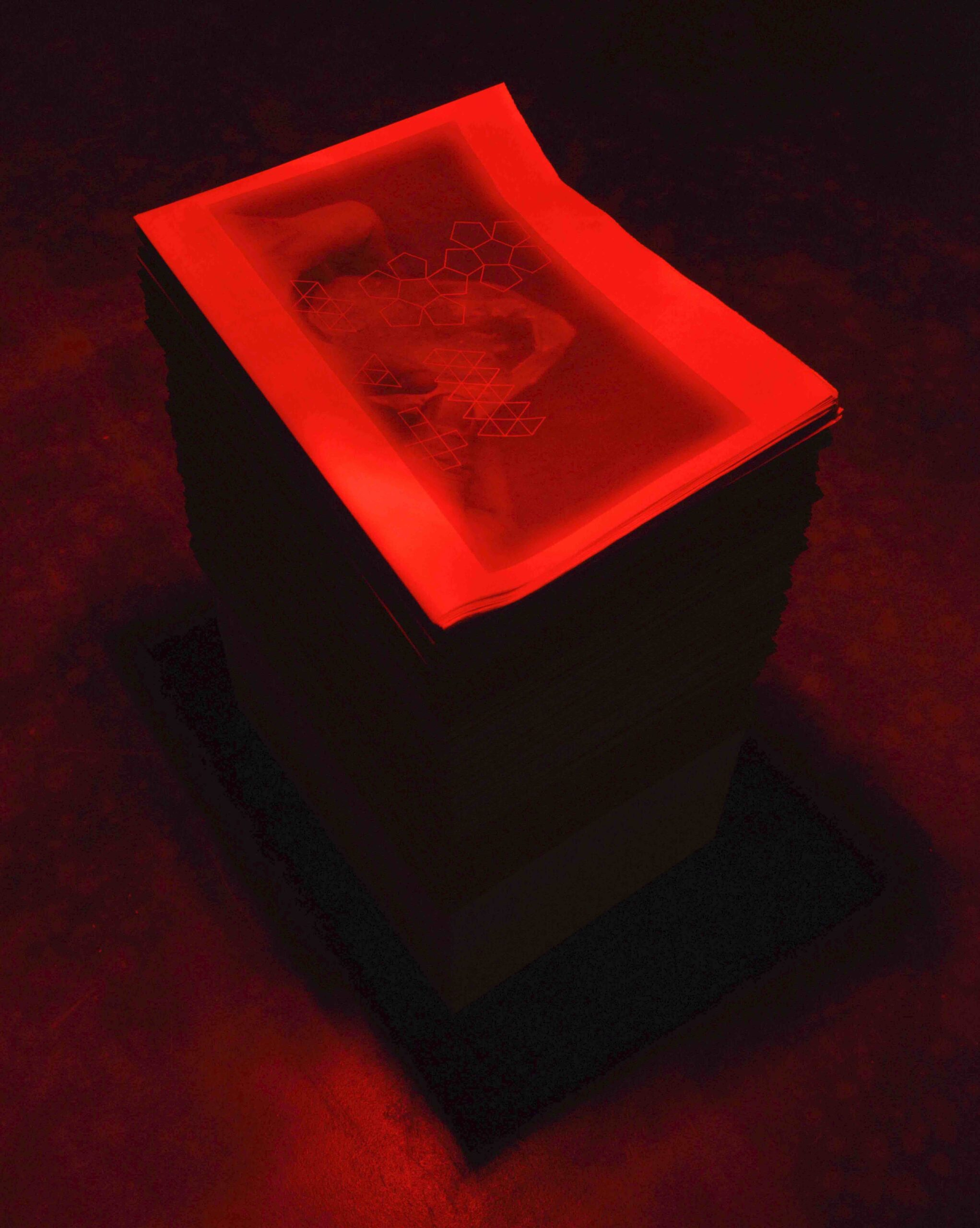 An image of a stack of Soot Breath Corpus Infinitum A3 publications about 1m in height, under a red light