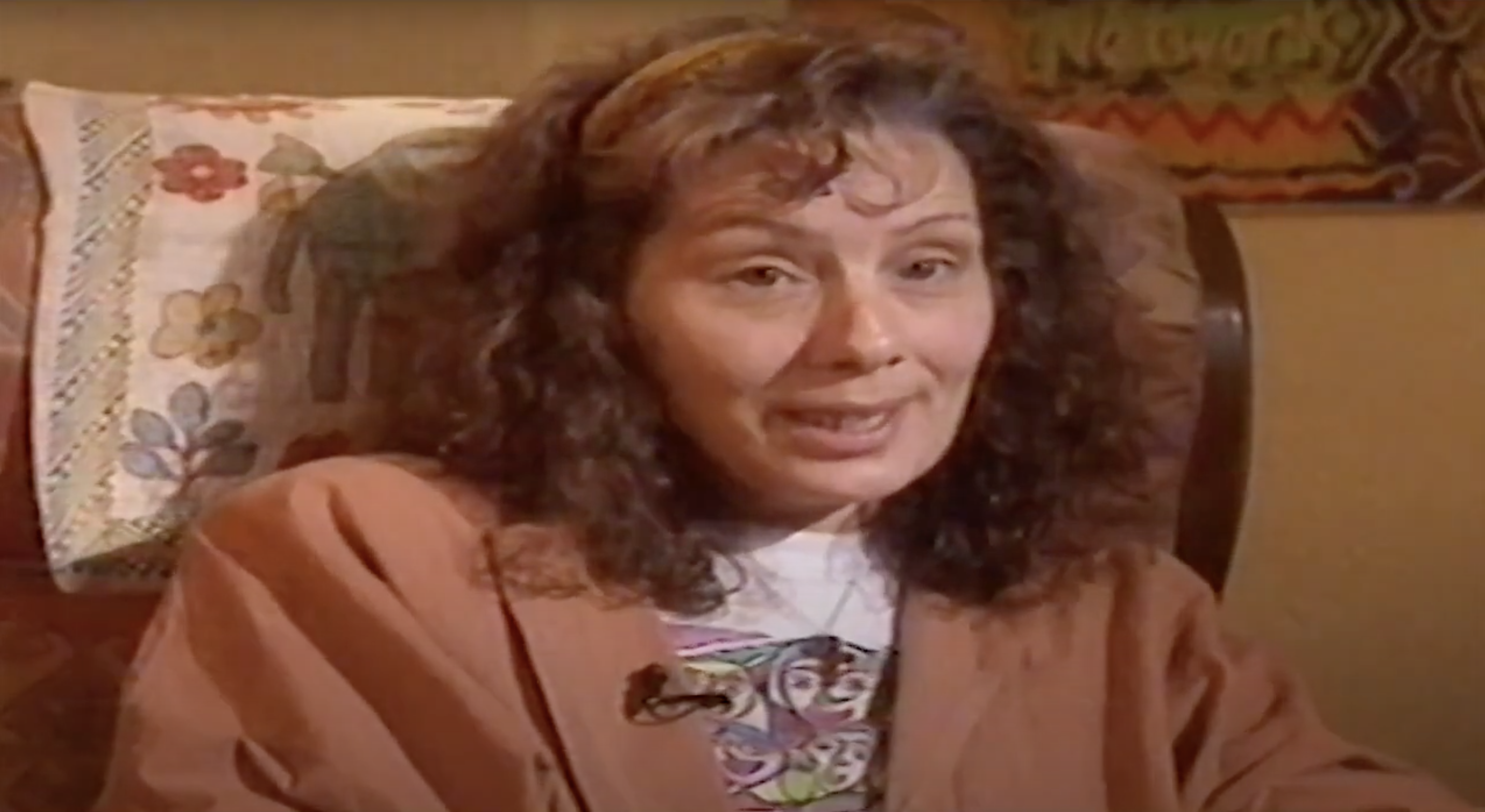 A woman with brown curly hair is sitting in an armchair, talking to the camera.