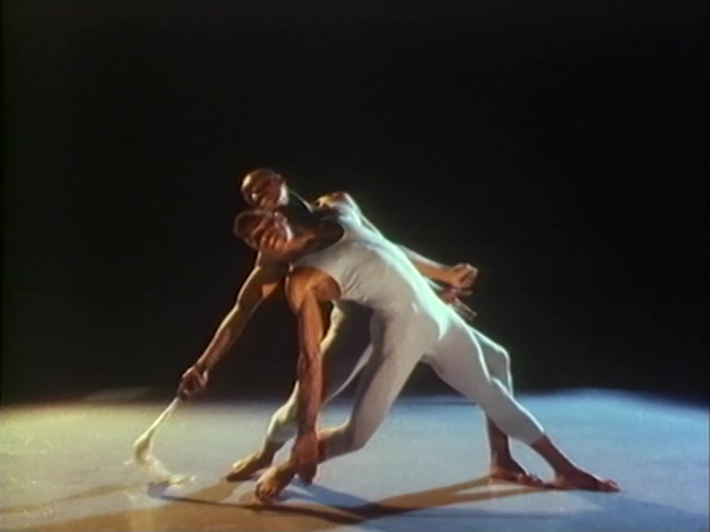 A still from the film rage and desire, the image is of medium quality, slightly blurred and hazy. Two black men in grey leotards pose athletically. They are contemporary dancers mid routine. They are in a dark room, their bodies and the surrounding floor illuminated by spotlight. Their legs are stretched into a lunge and they both lean backwards in unison. The body of the dancer in the foreground partially obstructs his partner, as if they are one being with four legs, two heads and four arms. Both right arms are stretched towards the floor and their left hands are clasped together.